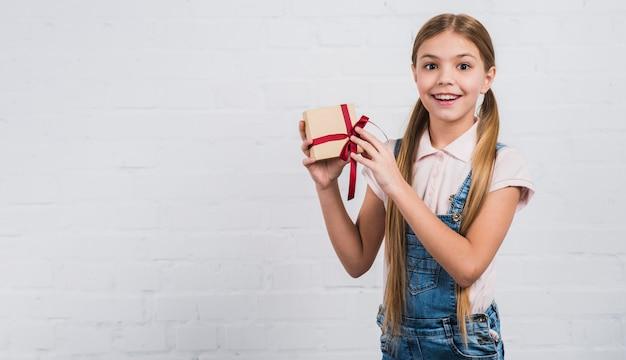Aufgeregtes glückliches mädchenkind, das eingewickeltes geschenk in der hand darstellt