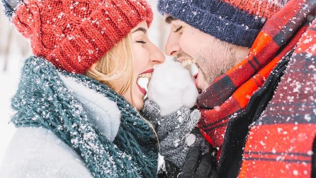 Aufgeregtes glückliches paar, das schneeball im holz leckt