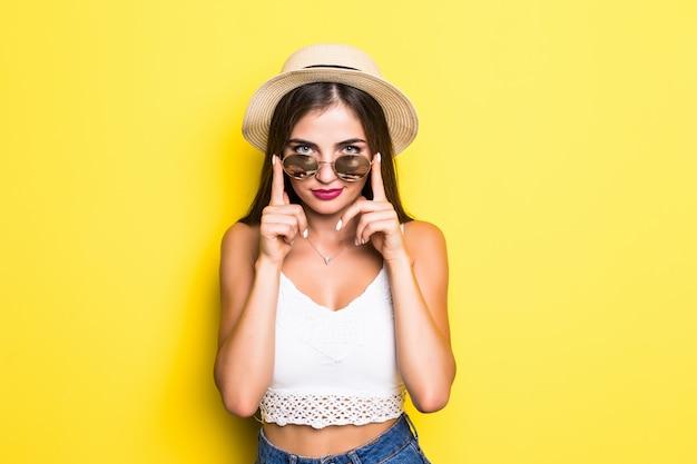 Aufgeregtes hipster-mädchen mit hut und sonnenbrille auf gelber wand