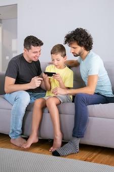 Aufgeregtes jungenspiel auf handy. zwei väter helfen sohn, online-app auf zelle zu verwenden. vertikaler schuss. familie zu hause und kommunikationskonzept