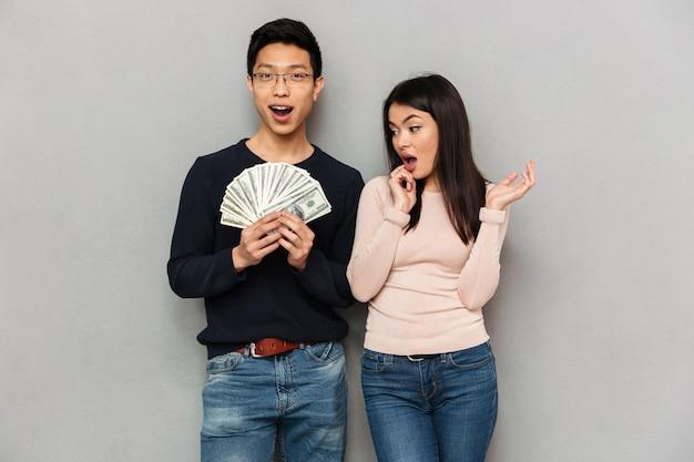 Aufgeregtes junges asiatisches liebespaar, das geld hält.
