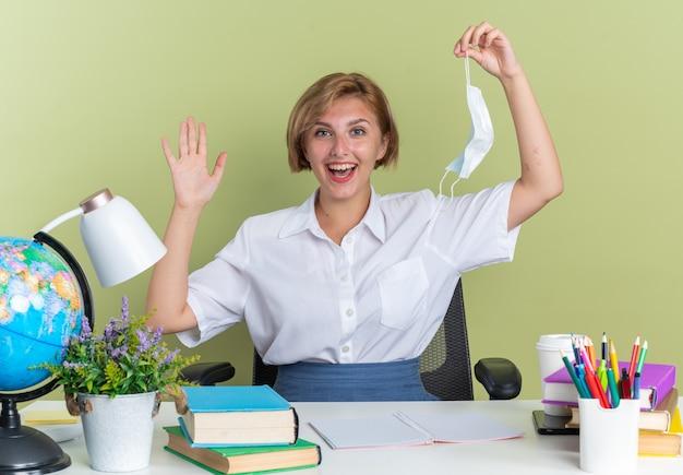 Aufgeregtes junges blondes studentenmädchen, das am schreibtisch mit schulwerkzeugen sitzt und in die kamera schaut, die schutzmaske und leere hand isoliert auf olivgrüner wand zeigt