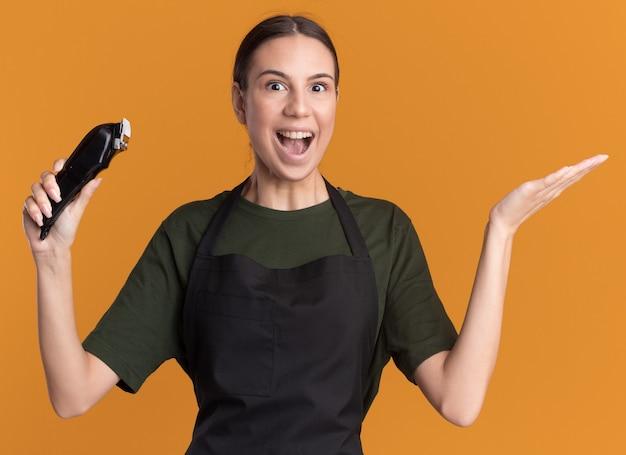 Aufgeregtes junges brünettes friseurmädchen in uniform hält die hand offen und hält haarschneidemaschinen isoliert auf oranger wand mit kopierraum