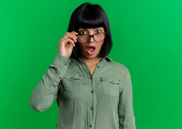 Aufgeregtes junges brünettes kaukasisches mädchen hält optische brille, die kamera lokalisiert auf grünem hintergrund mit kopienraum betrachtet