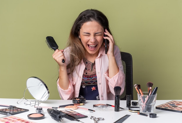 Aufgeregtes junges brünettes mädchen, das am tisch mit make-up-tools sitzt und am telefon spricht und einen kamm hält