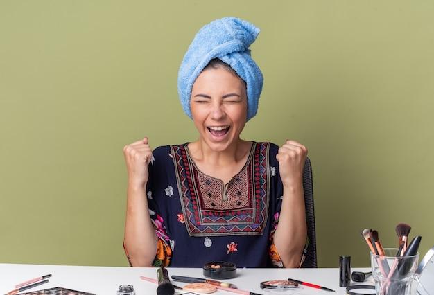 Aufgeregtes junges brünettes mädchen mit eingewickelten haaren im handtuch, das am tisch mit make-up-tools sitzt und die fäuste hochhält