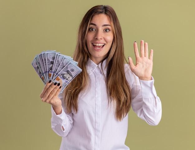 Aufgeregtes junges hübsches kaukasisches mädchen hält geld und zeigt fünf auf olivgrün