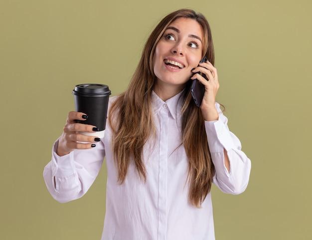 Aufgeregtes junges hübsches kaukasisches mädchen hält pappbecher und telefoniert mit blick auf die seite