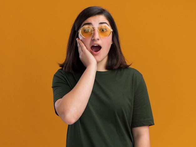 Aufgeregtes junges hübsches kaukasisches mädchen in der sonnenbrille legt hand auf gesicht und schaut kamera auf orange an