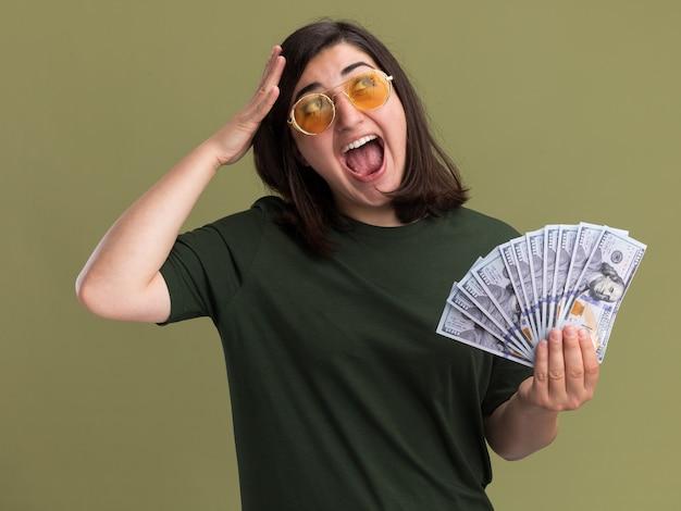 Aufgeregtes junges hübsches kaukasisches mädchen in sonnenbrille legt die hand auf den kopf und hält geld, das auf die seite schaut