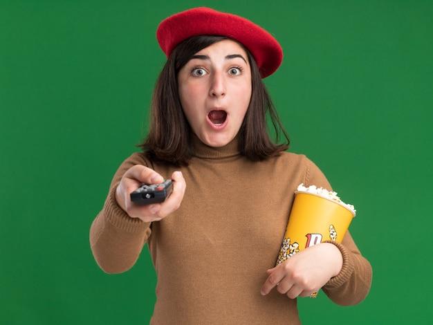 Aufgeregtes junges hübsches kaukasisches mädchen mit baskenmütze, das tv-controller und popcorn-eimer hält, isoliert auf grüner wand mit kopierraum