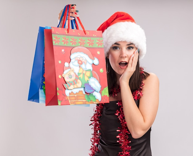 Aufgeregtes junges hübsches kaukasisches mädchen mit weihnachtsmütze und lametta-girlande um den hals, das weihnachtsgeschenktüten hält, die hand auf dem gesicht halten und die kamera einzeln auf weißem hintergrund betrachten