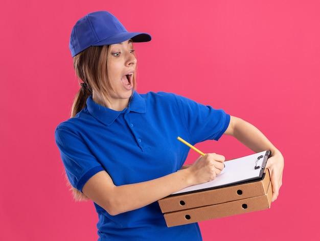 Aufgeregtes junges hübsches liefermädchen in uniform hält pizzaschachteln und schreibt auf zwischenablage mit stift auf rosa