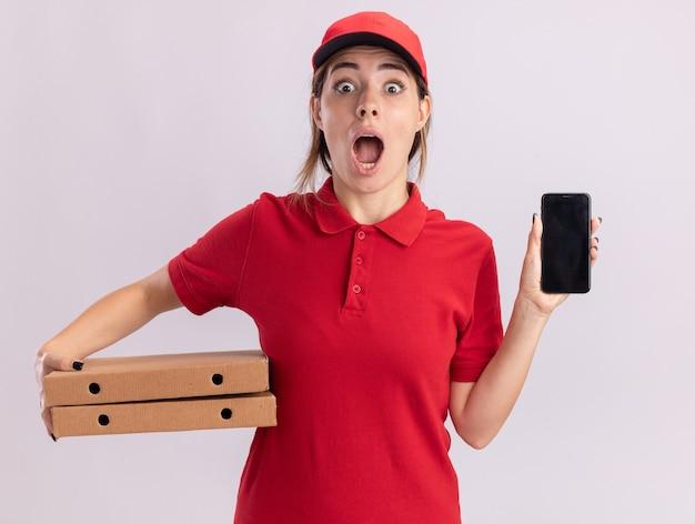 Aufgeregtes junges hübsches liefermädchen in uniform hält pizzaschachteln und telefon auf weiß