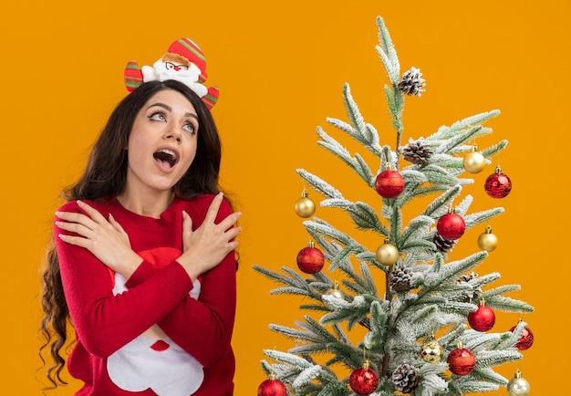 Aufgeregtes junges hübsches mädchen, das weihnachtsmann-stirnband und pullover trägt