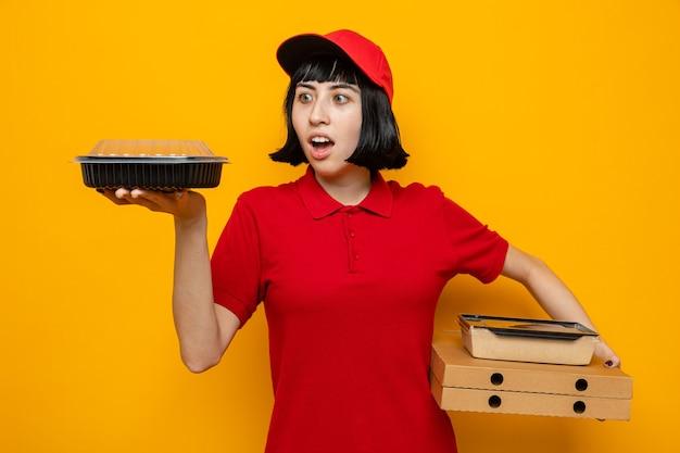 Aufgeregtes junges kaukasisches liefermädchen, das lebensmittelbehälter und verpackung auf pizzakartons hält