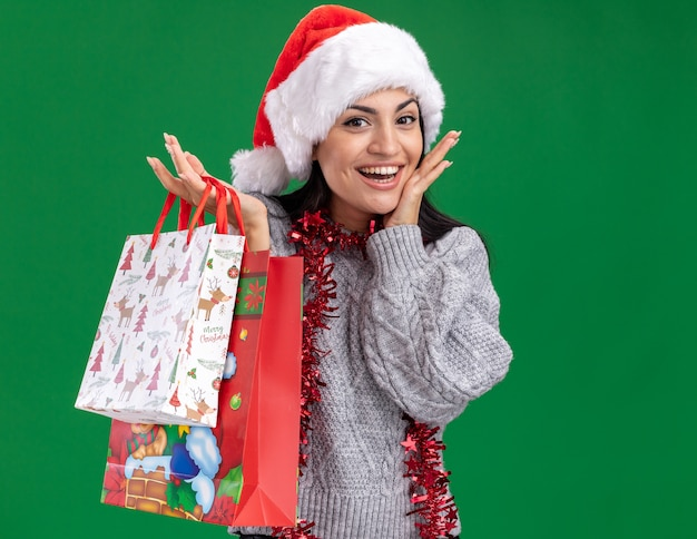 Aufgeregtes junges kaukasisches mädchen, das weihnachtsmütze und lametta-girlande um den hals hält, der weihnachtsgeschenktüten hält, die kamera berühren gesicht lokalisiert auf grünem hintergrund betrachten