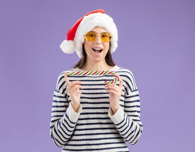 Aufgeregtes junges kaukasisches mädchen in sonnenbrille mit weihnachtsmütze, die zuckerstange hält