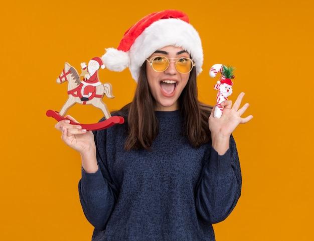 Aufgeregtes junges kaukasisches mädchen in sonnenbrille mit weihnachtsmütze hält den weihnachtsmann auf schaukelpferddekoration und zuckerstange einzeln auf orangefarbener wand mit kopierraum