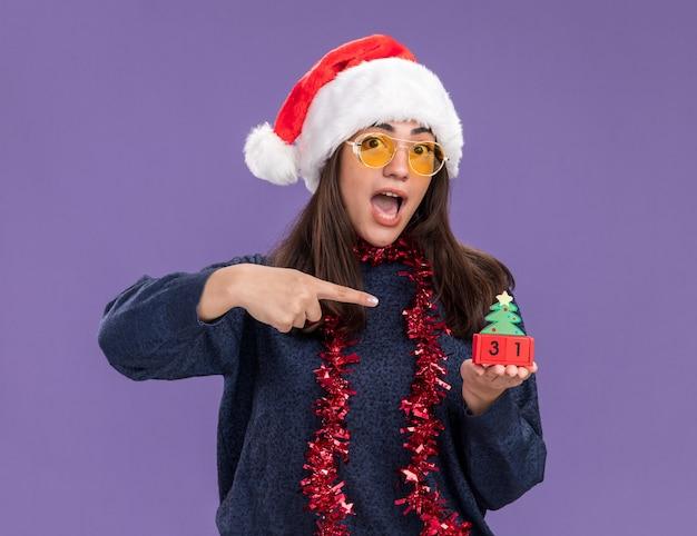 Aufgeregtes junges kaukasisches mädchen in sonnenbrille mit weihnachtsmütze und girlande um hals hält und zeigt auf weihnachtsbaumverzierung lokalisiert auf lila hintergrund mit kopienraum