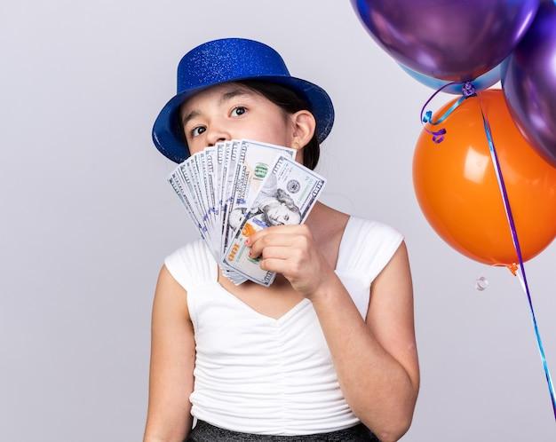 Aufgeregtes junges kaukasisches mädchen mit blauem partyhut, das mit heliumballons steht und geld isoliert auf weißer wand mit kopienraum hält