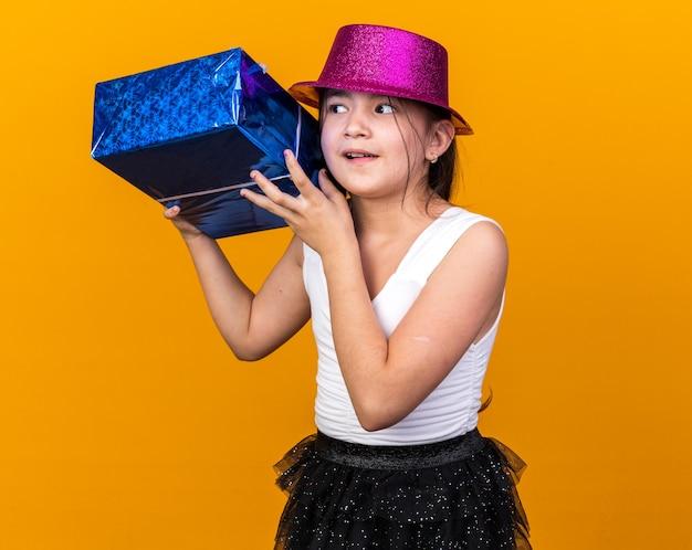 Aufgeregtes junges kaukasisches mädchen mit lila partyhut, das eine geschenkbox in der nähe des ohrs hält und versucht, isoliert auf einer orangefarbenen wand mit kopierraum zu hören?