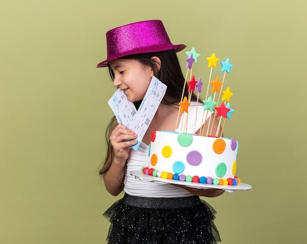Aufgeregtes junges kaukasisches mädchen mit lila partyhut, das geburtstagskuchen und flugtickets hält, die mit geschlossenen augen isoliert auf olivgrüner wand mit kopierraum stehen