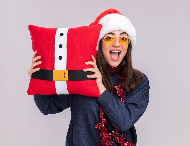 Aufgeregtes junges kaukasisches mädchen mit weihnachtsmütze und girlande um hals hält verziertes kissen lokalisiert auf weißem hintergrund mit kopienraum