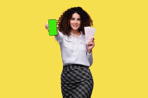 Aufgeregtes junges lockiges mädchen, das lottoscheine und smartphone mit leerem grünem bildschirm lokalisiert über gelbem hintergrund hält