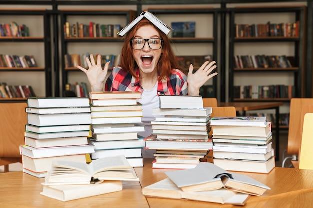 Aufgeregtes junges mädchen, das am bibliothekstisch sitzt