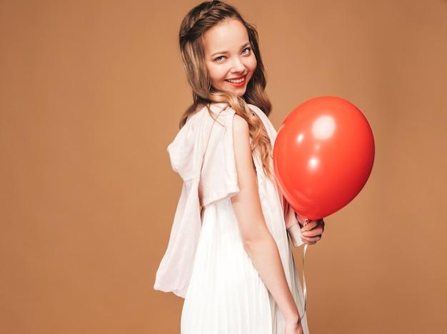 Aufgeregtes junges mädchen, das im weißen kleid des modischen sommers aufwirft. frauenmodell mit der roten ballonaufstellung. bereit für die party