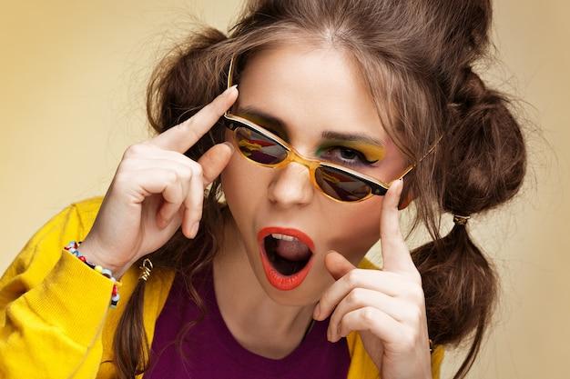 Aufgeregtes junges mädchen, das retro-sonnenbrille trägt