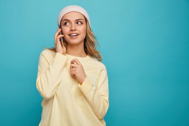 Aufgeregtes junges mädchen, das wintermütze trägt, die am telefon spricht, das oben schaut