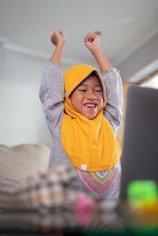 Aufgeregtes junges muslimisches kind beim online-lernen von zu hause mit laptop