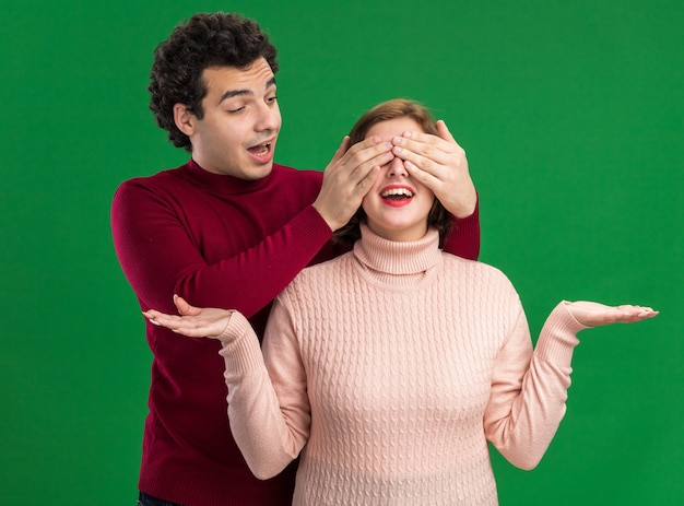 Aufgeregtes junges paar am valentinstag mann, der hinter einer frau steht und sie betrachtet, die ihre augen mit den händen bedeckt, und sie zeigt leere hände einzeln auf grüner wand