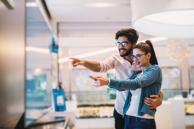 Aufgeregtes junges paar, das großen fernsehbildschirm für ihren neuen tech-laden home.at betrachtet