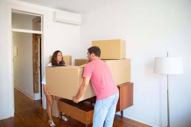 Aufgeregtes junges paar, das in eine neue wohnung zieht und kartons vorsichtig trägt
