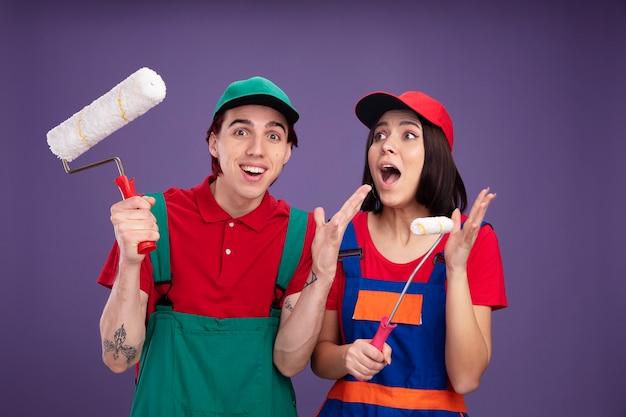 Aufgeregtes junges paar in bauarbeiteruniform und mütze mit farbroller, das leere hand zeigt, mädchen, das auf die seite schaut