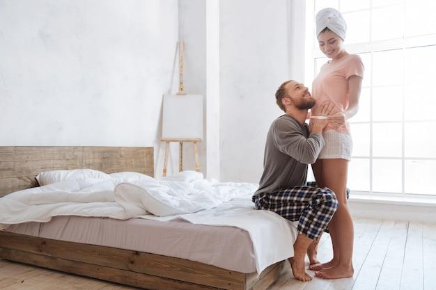 Aufgeregtes junges paar kann seine wahren gefühle nicht im inneren behalten, nachdem es positive schwangerschaftstestergebnisse gesehen hat