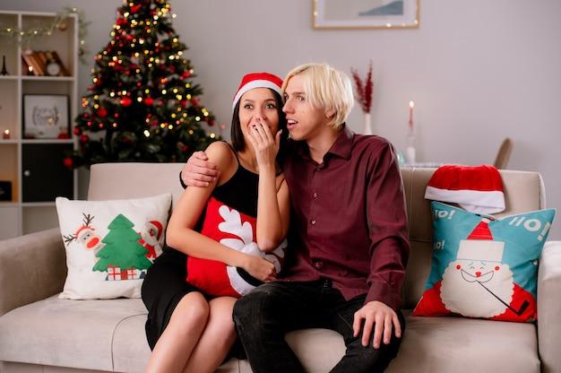 Aufgeregtes junges paar zu hause zur weihnachtszeit mit weihnachtsmütze auf sofa im wohnzimmer kerl umarmt ihr mädchen, das die hand auf mund hält, beide fernsehmädchen, das weihnachtskissen hält