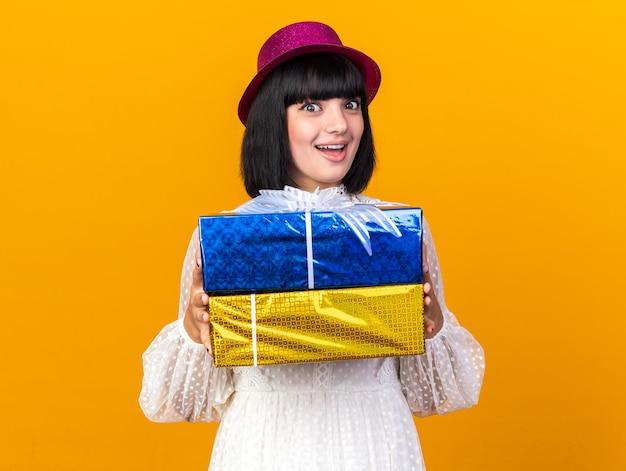 Aufgeregtes junges partymädchen mit partyhut, das geschenkpakete hält, die vorne isoliert auf oranger wand schauen