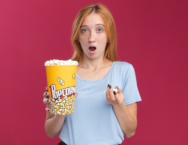 Aufgeregtes junges rothaariges ingwermädchen mit sommersprossen, das popcorneimer hält holding