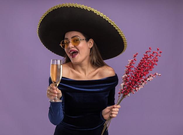 Aufgeregtes junges schönes mädchen, das blaues kleid und brille mit sombrero hält ebereschenzweig mit glas champagner lokalisiert auf lila hintergrund trägt