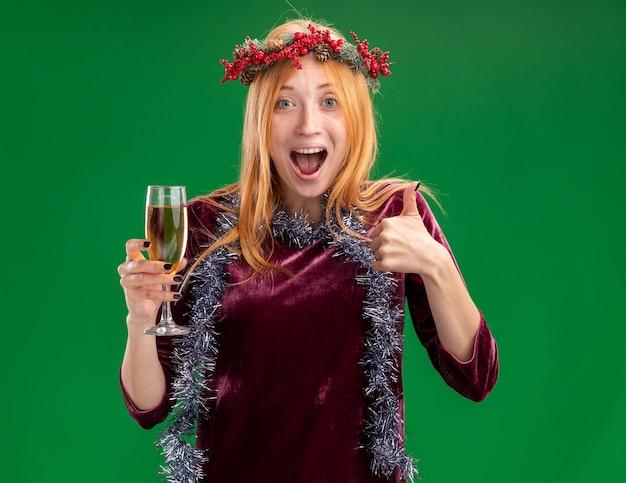 Aufgeregtes junges schönes mädchen, das rotes kleid mit kranz und girlande am hals hält glas des champagners zeigt daumen oben auf grünem hintergrund