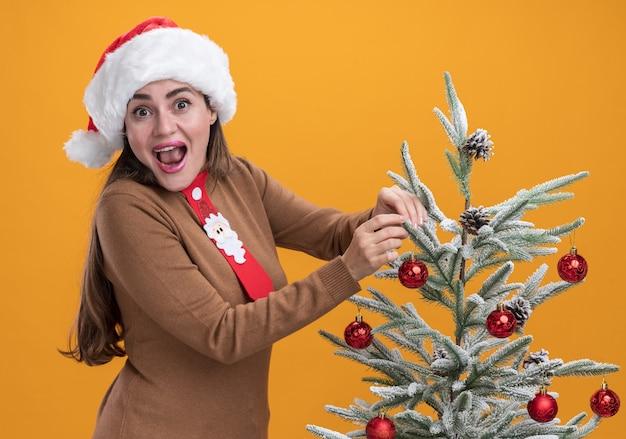 Aufgeregtes junges schönes mädchen, das weihnachtshut mit krawatte trägt, die nahe weihnachtsbaum lokalisiert auf orange hintergrund steht