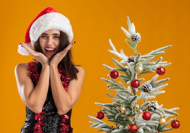 Aufgeregtes junges schönes mädchen, das weihnachtsmütze mit girlande am hals trägt, der nahe weihnachtsbaum hält hände um gesicht lokalisiert auf orange wand steht