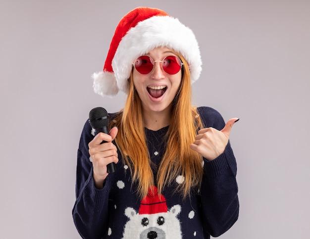 Aufgeregtes junges schönes mädchen, das weihnachtsmütze und brille hält, die mikrofon hält daumen oben auf weißem hintergrund