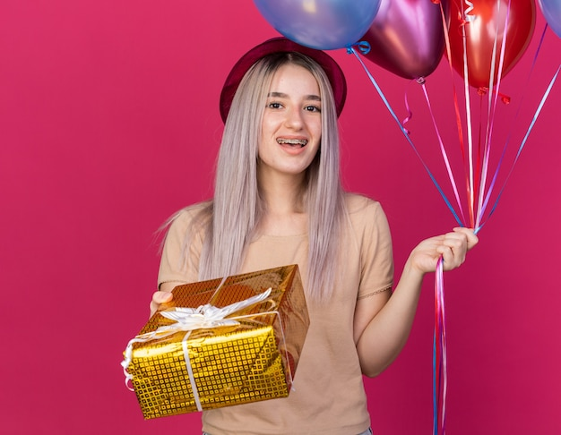 Aufgeregtes junges schönes mädchen mit partyhut mit zahnspangen, die luftballons mit geschenkbox halten