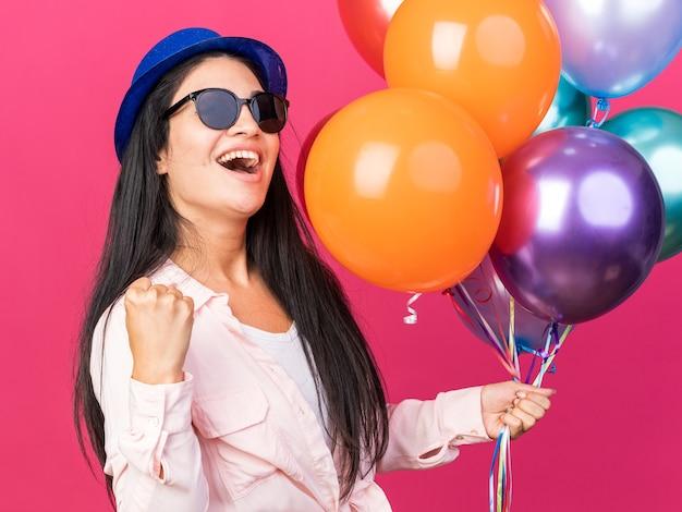 Aufgeregtes junges schönes mädchen mit partyhut und brille mit luftballons, die eine ja-geste zeigen
