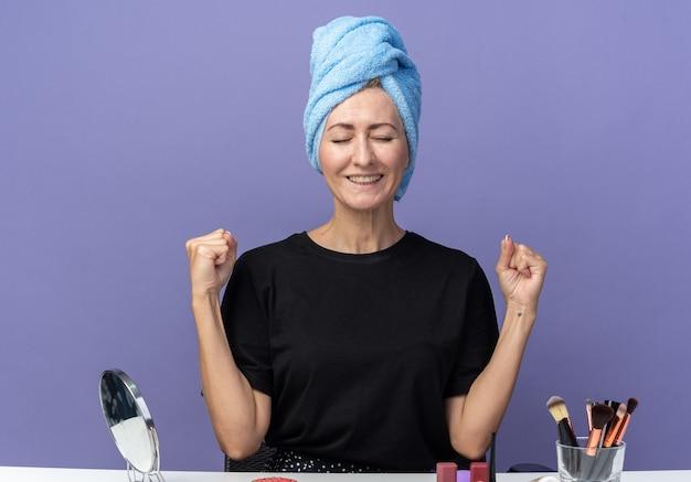 Aufgeregtes junges schönes mädchen sitzt am tisch mit make-up-tools und wischt sich die haare im handtuch ab und zeigt ja-geste einzeln auf blauer wand